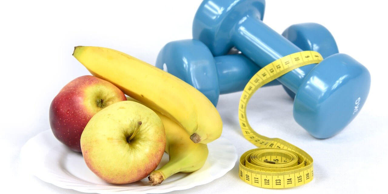 Fruits in a bowl next to the dumbbell and measuring tape